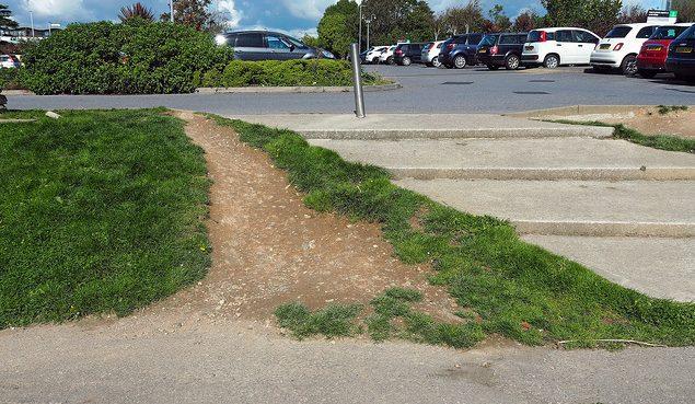 Escalera y camino alternatrivo sobre la hierba hecho por las personas al caminar evitando la escalera