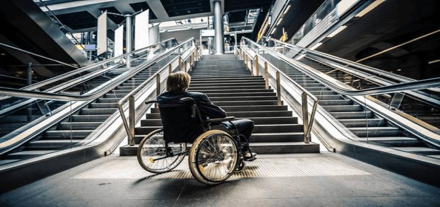 persona usuaria de silla de ruedas frente a una escalera