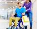 Chico en silla de ruedas empujado por una chica, haciendo compras en un mall