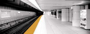 Vista de un anden de metro en blanco y negro con piso podotactil amarillo